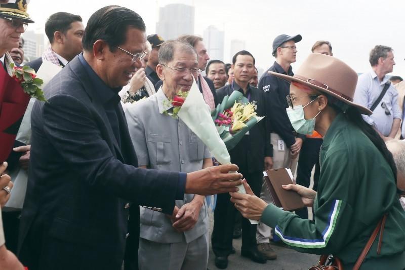 豪華郵輪「威士特丹號」14日在柬埔寨停靠後,上千名乘客獲准下船,柬埔寨總理洪森(圖左)向下船旅客獻上玫瑰花束。(美聯社)
