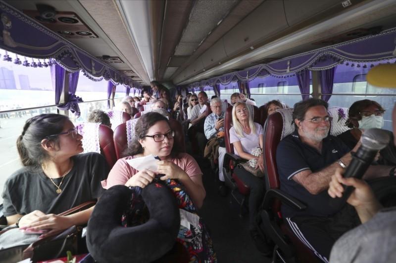 乘客下船後由巴士載送。(美聯社)