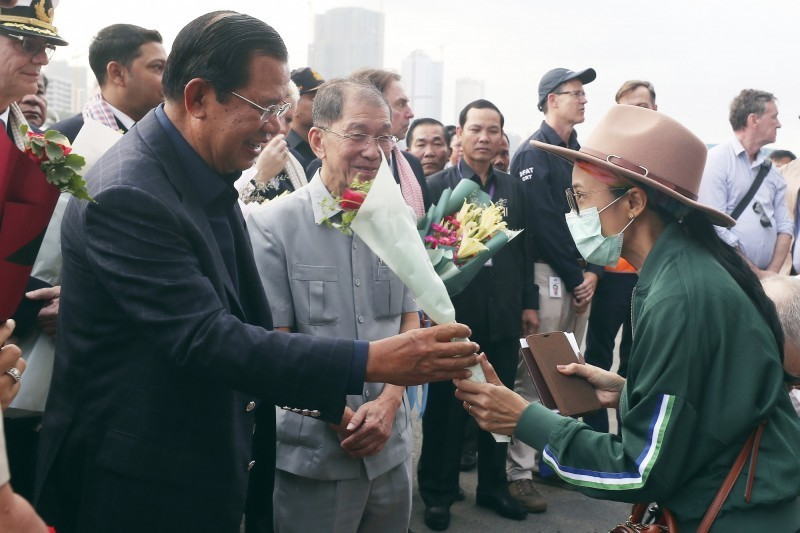 豪華郵輪「威士特丹號」14日在柬埔寨停靠後,上千名乘客已開始下船,柬埔寨總理洪森(圖左)向下船旅客獻上玫瑰花束。(美聯社)