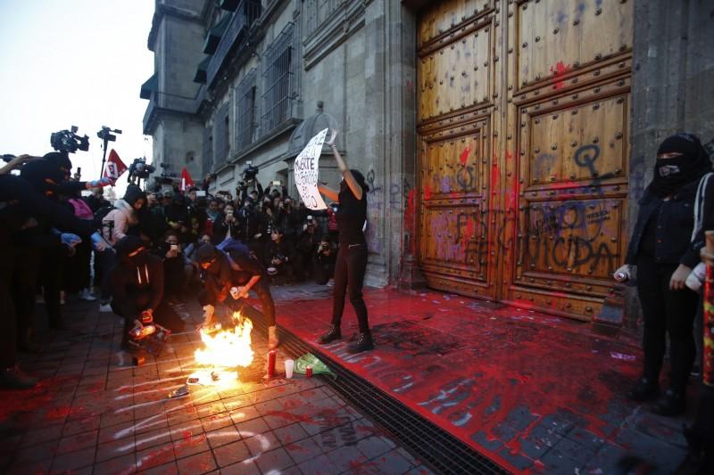 示威者在國家宮前潑上假血,並以西班牙語寫上女性屠殺國。(美聯社)