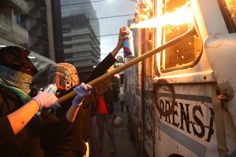 示威者引燃報社的車子。(歐新社)