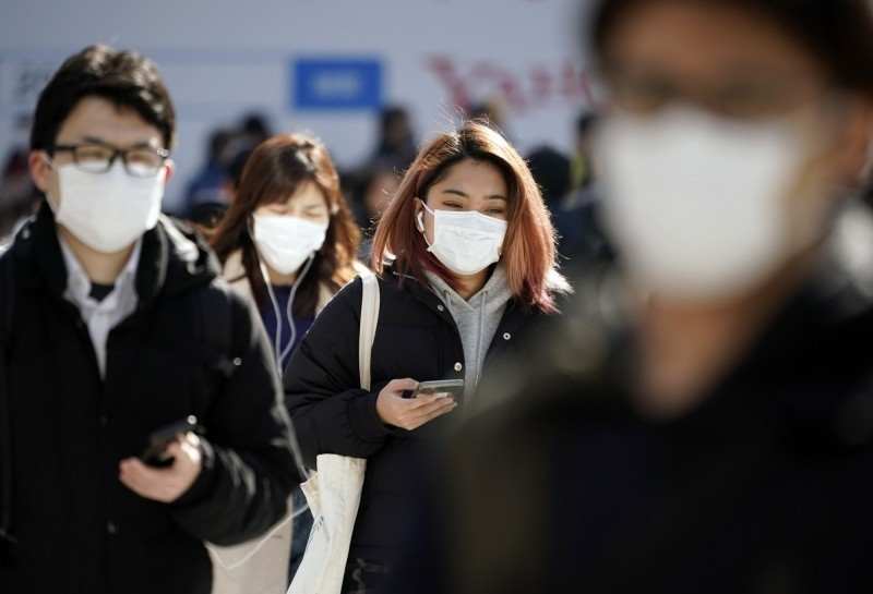 日本15日晚間再增一起武漢肺炎病例,是前例確診感染的60多歲男性患者的妻子。圖為日本街頭行人都戴著口罩。(歐新社)