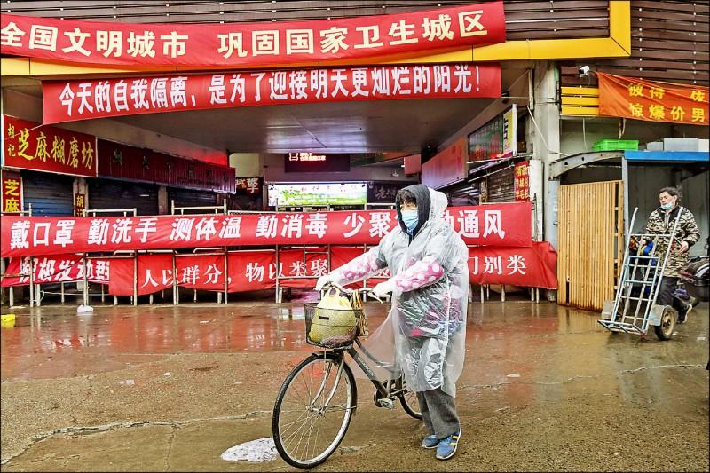 「武漢肺炎」來襲,中國各大城一一淪陷,上海市一處市集十五日門可羅雀,外頭掛滿防疫宣導布條,只見寥寥可數的路人戴口罩經過。(彭博)