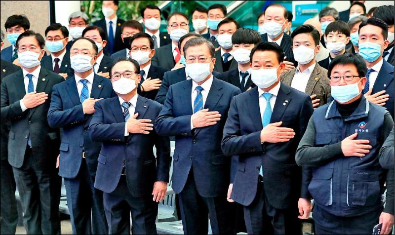 圖為6日在釜山市政府,南韓總統文在寅(前排右3)參加一場創造就業計畫的啟動儀式時,現場出席的官員均戴口罩。(美聯社)