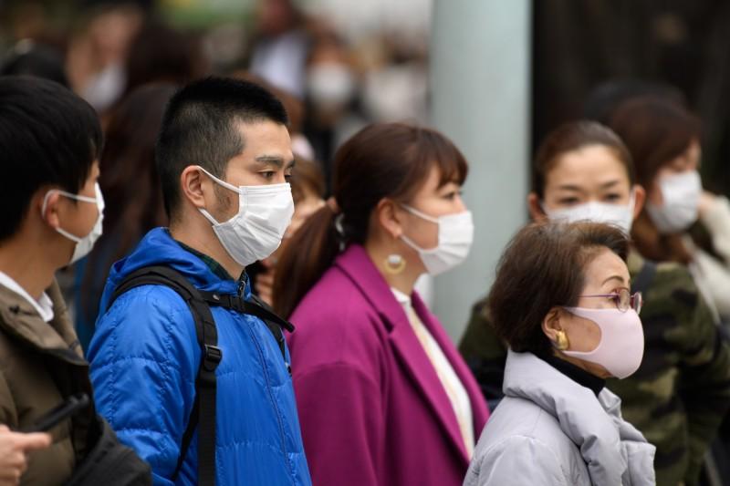 日本疫情持續上升,東京民眾全都戴上口罩以防疫。(彭博)