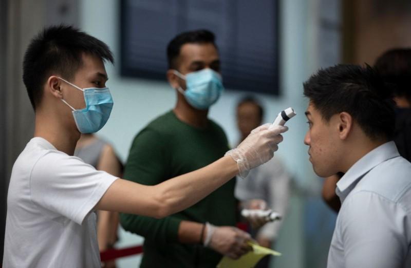 新加坡為中國之外確診人數最高的國家之一,圖為新加坡民眾進入商業大樓接受測溫。(歐新社)