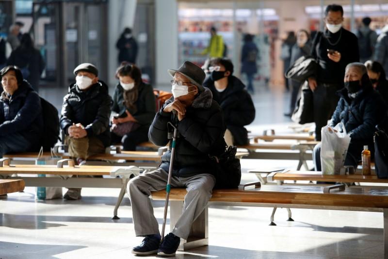 南韓當局考慮將新型冠狀病毒檢疫擴大至一般肺炎患者。圖為南韓民眾戴口罩防疫。(路透)