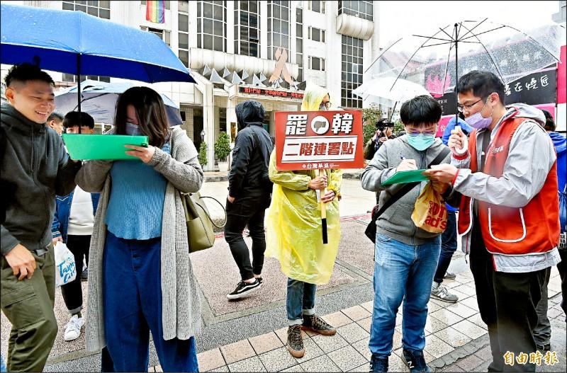 台灣基進昨北上在西門町發起罷韓連署,雖然下著細雨,仍吸引不少民眾冒雨填寫連署書。(記者朱沛雄攝)