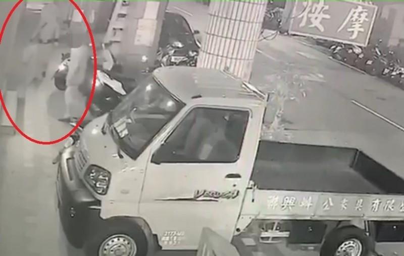 監視器畫面拍下犯嫌提著汽油桶走向按摩店。(記者王宣晴翻攝)