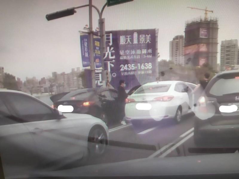搶嫌身穿黑衣,戴著口罩,入侵阮男的白色車內搶劫。(記者張瑞楨翻攝)