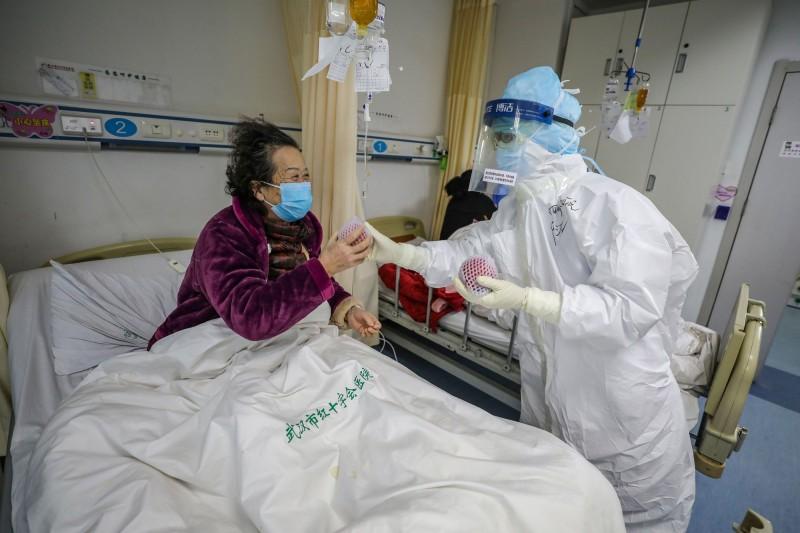 中國媒體傍晚證實,武漢市今天上午針對武漢肺炎疫情,再度展開號稱「拉網式」的清查,為期3天。圖為16日武漢紅十字會醫院病房內醫護人員遞水果給武漢肺炎病患的畫面。(法新社)