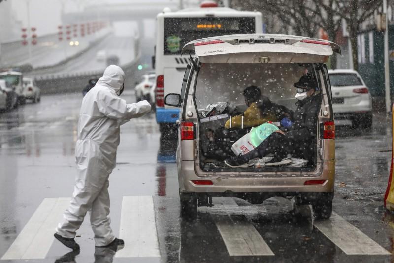 中國湖北省飽受武漢肺炎疫情肆虐,時序已經進入新春,卻仍深陷在寒風中;圖為15日武漢市某家指定收治感染者的醫院,工作人員身穿全套防護衣在雪中接收患者。(美聯社)
