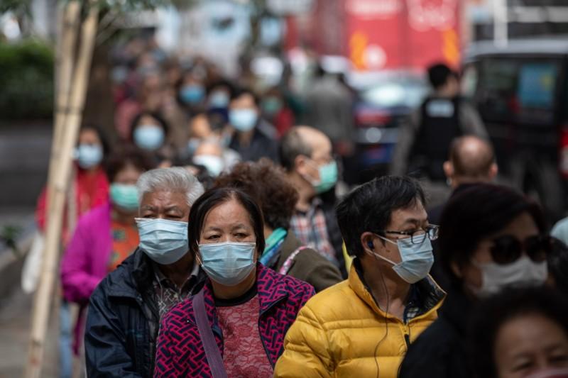 2名涉嫌違反居家隔離要求的香港居民,最高將面臨6個月有期徒刑、罰款2.5萬港元(約新台幣9.6萬元)。圖為香港領取口罩的人潮。(歐新社)