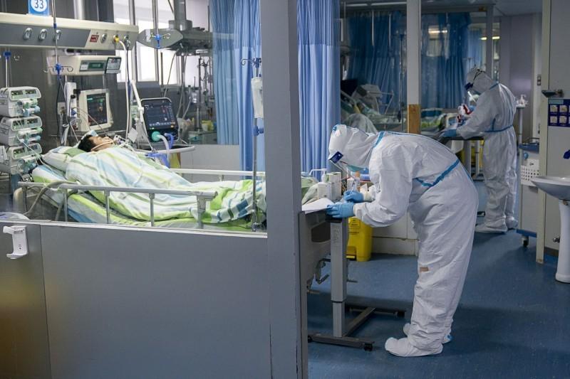 武漢肺炎疫情蔓延,中國首批患者遺體解剖驗屍已完成,分析報告最快10日內出爐。圖為武漢某醫院加護病房,醫護人員都穿上全副武裝隔離衣。(歐新社)