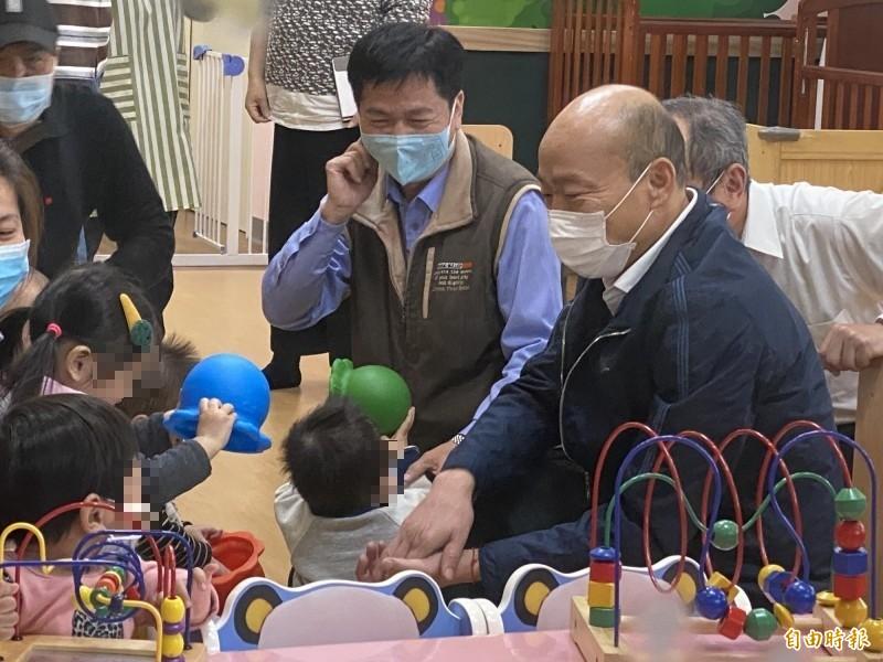 韓國瑜(右)與苓雅社區公托院童互動。(記者黃旭磊攝)