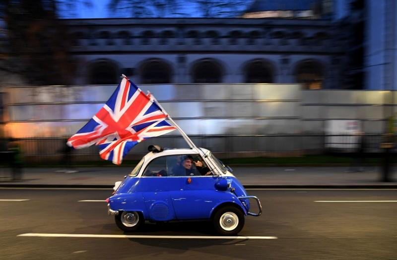 英國政府今(19)日宣布脫歐後的移民新政策,將不再發予「低技術工作者」簽證。圖為英國民眾揮旗慶祝脫歐。(法新社)