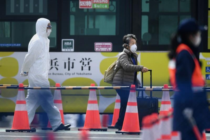19日,一名從鑽石公主號離開的乘客正拖著行李。(法新社)