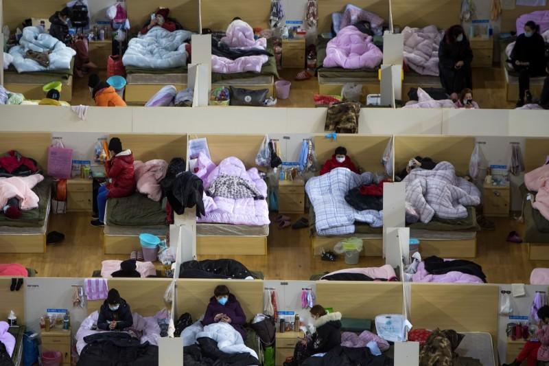 中國武漢爆發的新型冠狀病毒引發的肺炎(COVID-19,下稱武漢肺炎)疫情持續延燒。圖為確診患者在武漢市武漢體育中心改建的臨時醫院休息。(美聯社)