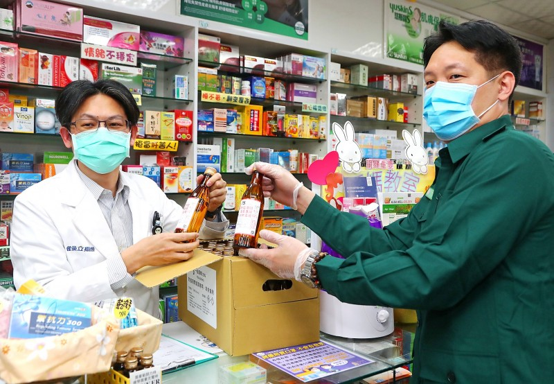 A Chunghwa Post driver delivers medical alcohol made by Taiwan Tobacco and Liquor Corp to a pharmacy yesterday. Photo: CNA
