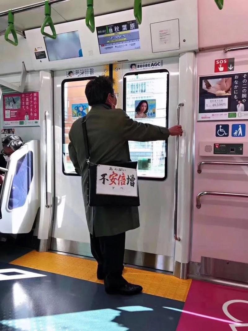 日本網友在地鐵上看見老翁自製「不安倍增」字牌。(圖擷自推特)