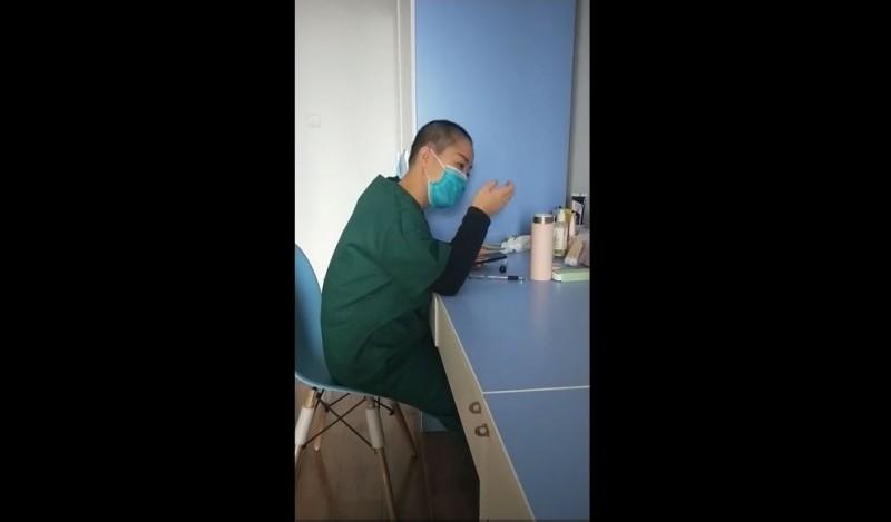 一名正在休息的女醫護邊看手機,邊下意識地用手將「頭髮」撥到耳後,撥完驚覺已經沒頭髮後,看著手愣住。(圖擷取自微博)