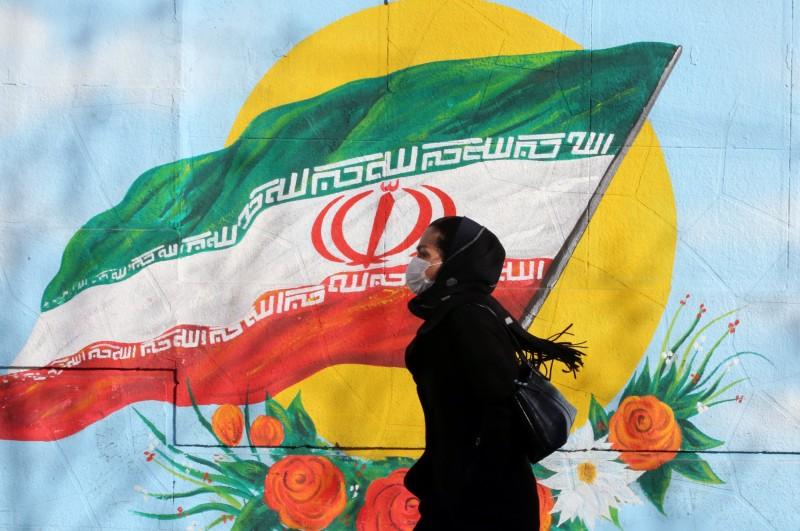 伊朗今(20)日晚間再宣布增加3名病患檢驗陽性,共計5例確診。中東地區目前僅有埃及、阿聯及伊朗傳出武漢肺炎確診病例。。圖為伊朗民眾戴口罩經過國旗壁畫。(歐新社)