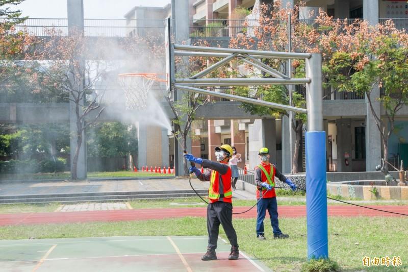 為提供師生安全環境,中市環保局進行校園及周邊環境消毒。(記者黃鐘山攝)