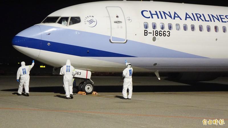 載運鑽石公主號19名台籍旅客返台的華航包機21日晚間返抵桃園機場,地勤人員全身防護裝備執行機坪作業。(記者朱沛雄攝)