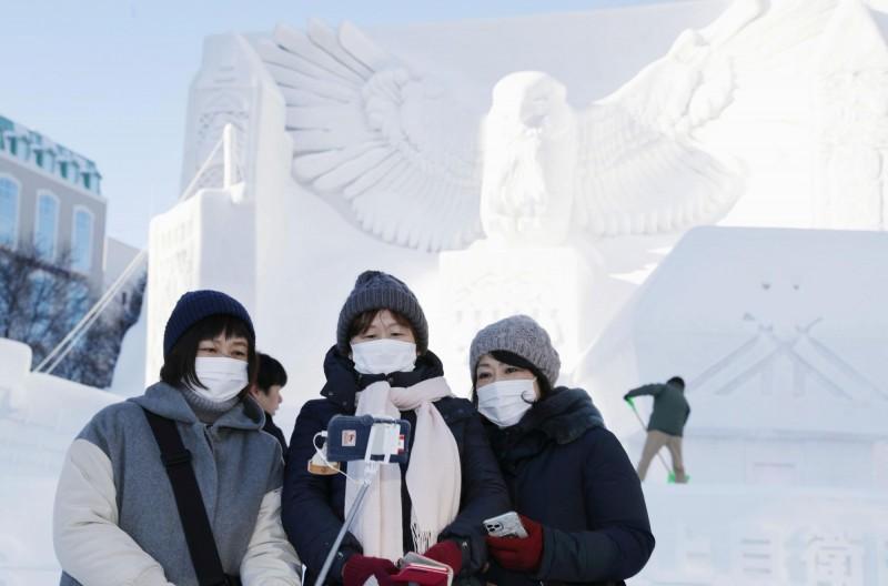 日本北海道今(21日)新增3起武漢肺炎確診病例,其中1人為未滿10歲的兒童,是日本最年幼的病患。圖為北海道札幌雪祭遊客戴上口罩防疫。(路透)