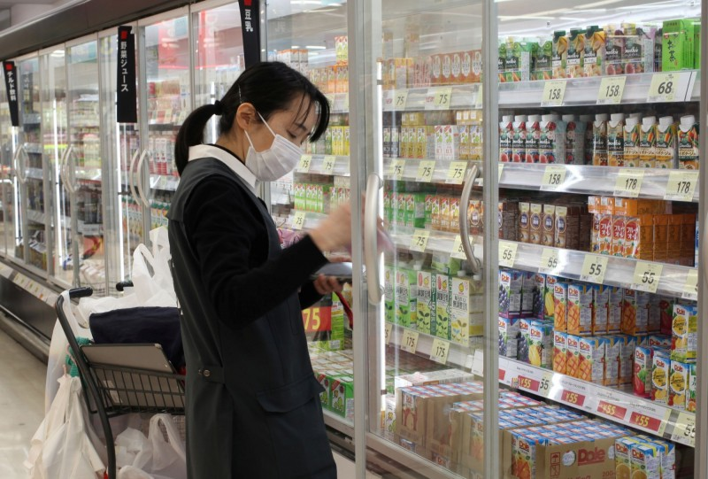 武漢肺炎疫情在全球快速蔓延,日本愛知縣名古屋市稍早再新增2例,雙雙都曾停留過確診前例曾到過的地方。圖為東京戴上口罩的店員,非當事人。(路透)