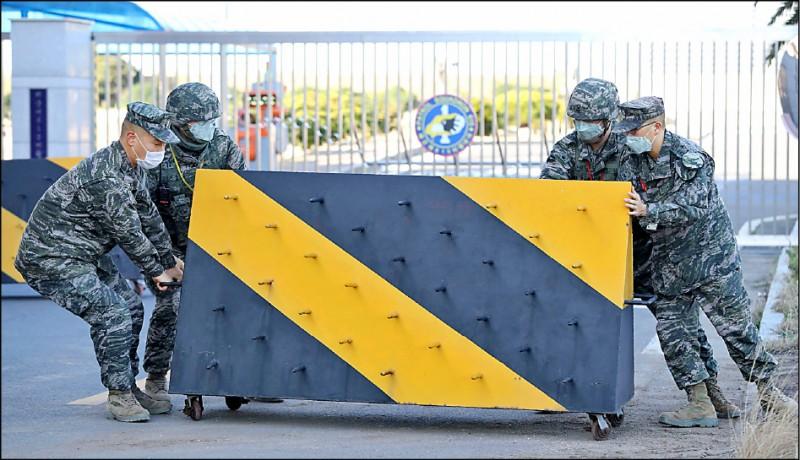 南韓海軍位於濟州島的某營區,二十日傳出一名軍官確診感染。營區內的海軍陸戰隊軍人廿一日在營區前擺放路障。(路透)