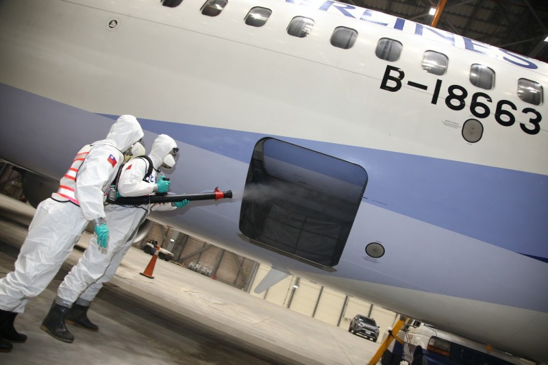 華航包機載運鑽石公主號旅客返台,在旅客下機後,國軍化學兵部隊立即進行機體各部位的消毒作業。(圖:國防部提供)