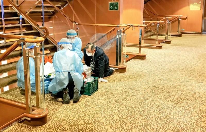 日本厚生勞動省前後至少派出90名職員登上鑽石公主號郵輪進行作業,這些人竟然沒有接受病毒篩檢就重返平日的工作崗位。圖為日本檢疫人員在鑽石公主號內部作業的情形。(路透)