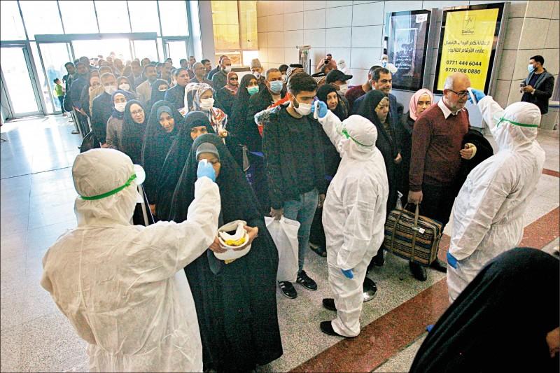 伊拉克南部納查夫國際機場的檢疫人員廿一日逐一對來自伊朗的乘客量測體溫。 (美聯社)
