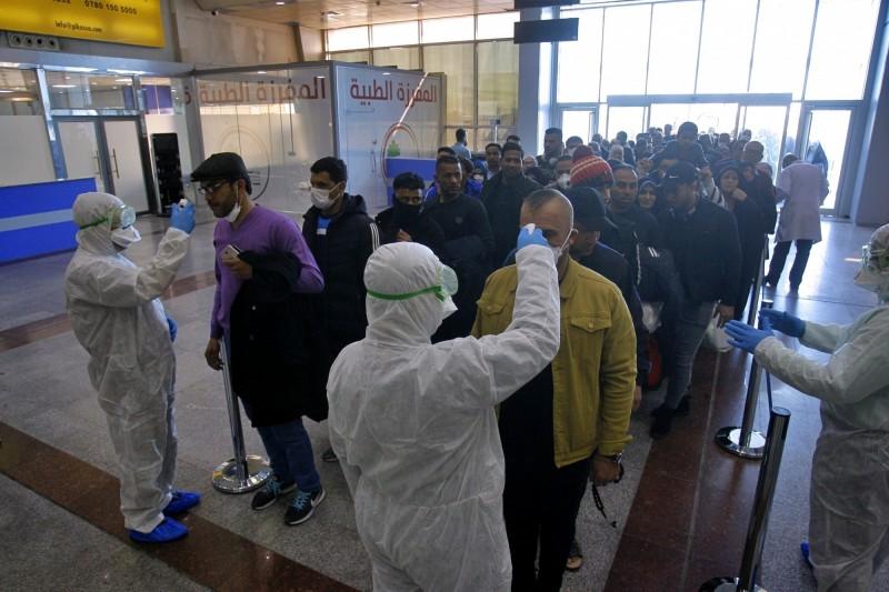 伊拉克防疫人員在機場對入境旅客量額溫檢疫。(美聯社)