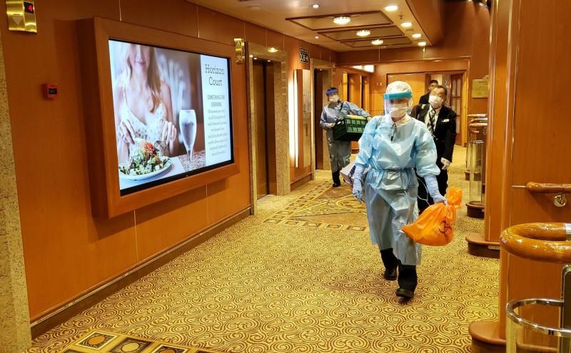 日本厚生勞動省表示,登上鑽石公主號作業的職員若擁有醫護資格,只要無症狀就不需篩檢。圖為登船作業的日本檢疫人員。(法新社)