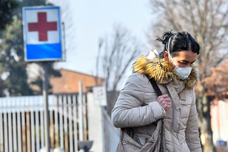 義大利武漢肺炎確診數今天突破百例,有2人死亡。圖中,義大利一名戴著口罩的女性從醫院離開。(路透檔案照)