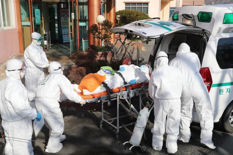 南韓的大南醫院精神病房爆發群聚感染,當局認為與患者長時間處在密閉空間有關。圖為醫護人員正要將患者從大南醫院轉送至其他醫院。(法新社)