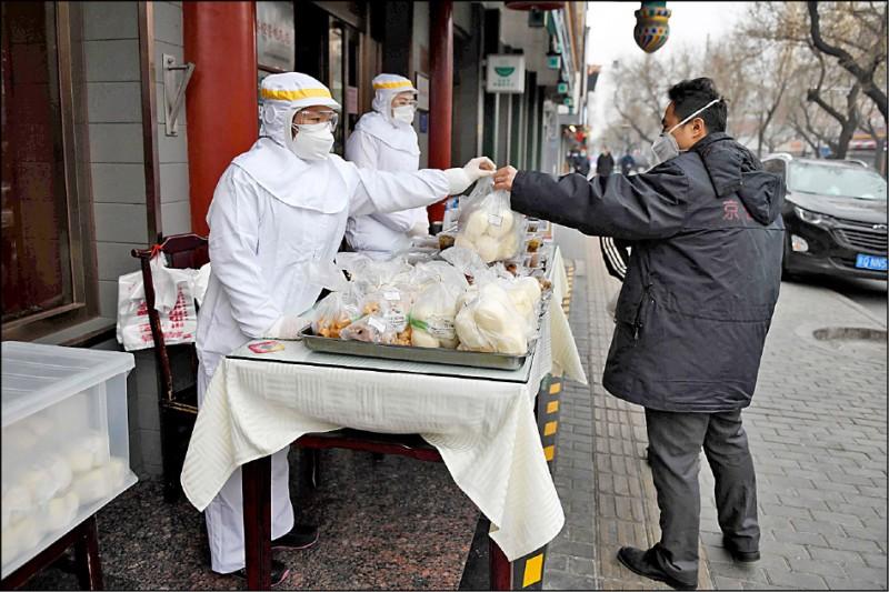 中國北京市的餐廳員工穿著全套防護衣,在店外販賣食物。(法新社)