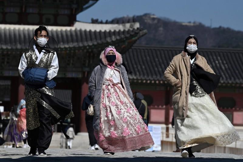 武漢肺炎情延燒,全球至少15個國家及地區對南韓實施入境管制。圖為身著韓服的遊客載上口罩,23日參訪首爾旅遊景點景福宮。(法新社)