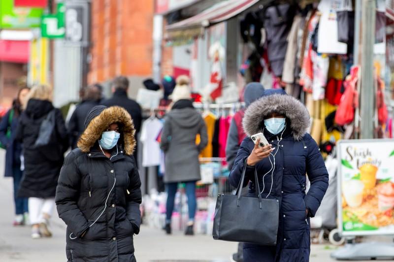 1名女子從中國搭機抵達加拿大安大略省,因為咳嗽就診後被驗出新型冠狀病毒陽性,加國當局正在聯繫座位在她附近的同機旅客。圖為安大略省行人紛紛戴上口罩。(路透)