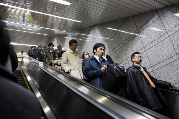 JR東日本一名50多歲男性員工確診感染武漢肺炎。圖為日本民眾排隊搭乘手扶梯。(法新社)
