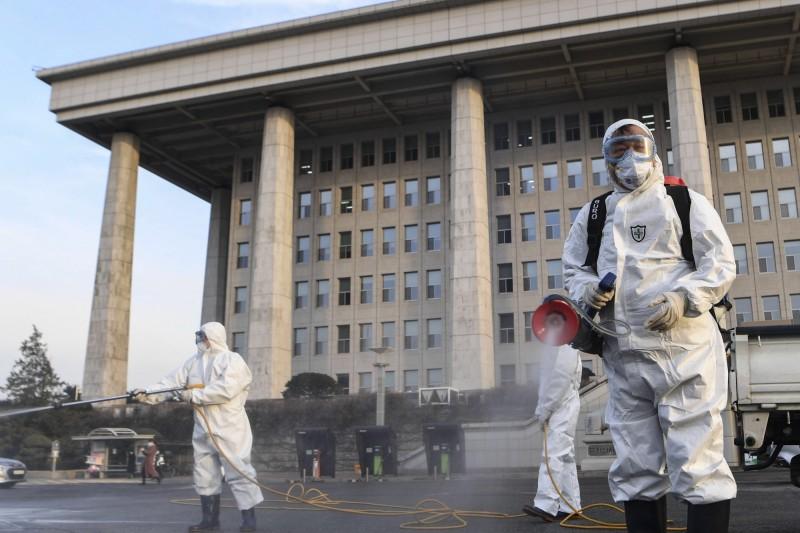 韓國教師聯合會主席河潤秀19日在國會舉辦公聽會,事後卻被驗出武漢肺炎確診;圖為24日防疫人員在韓國國會大廈外消毒。(歐新社)