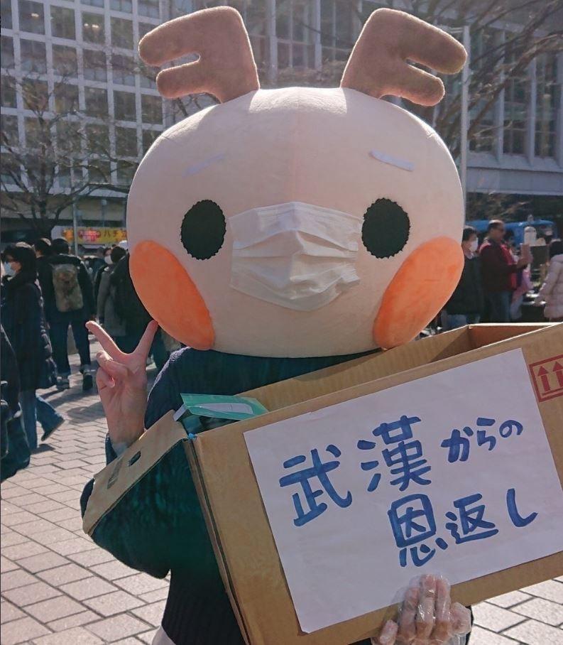 昨(23)日,有中國網友在日本澀谷車站附近拍到,一名身穿「小鹿裝」的女子正在發「愛心口罩」,裝著口罩的箱子上還寫著「來自武漢的報恩」,意外激起中國網友熱議。(圖擷取自微博)