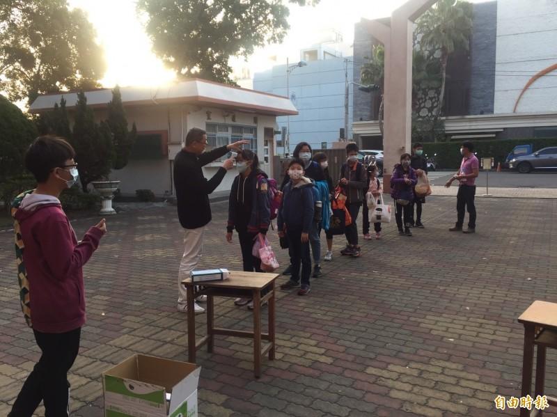 開學日,每個學童進入校園第一件事先量體溫。(記者林國賢攝)