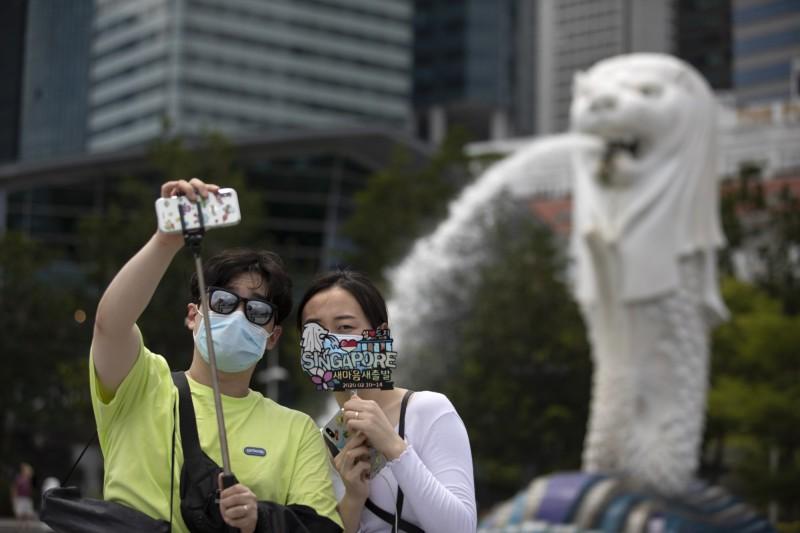 新加坡今(25)日宣布,將禁止任何曾至南韓大邱、清道郡2地的旅客入境或轉機,此外若韓國武漢肺炎(COVID-19)疫情持續擴張,不排除更進一步加強旅行限制。圖為遊客在新加坡魚尾獅前戴口罩合照。(歐新社)