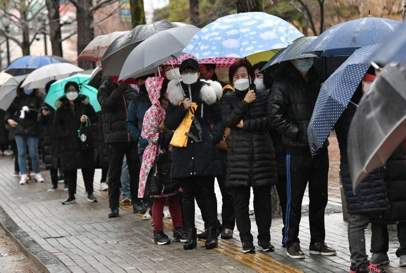 韓國的武漢肺炎疫情嚴重,但每日口罩產量的10%仍會出口。圖為韓國大邱民眾大排長龍購買口罩。(法新社)