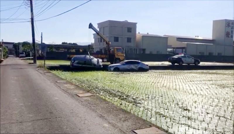 草屯鎮郊區產業道路上,兩汽車對撞後摔入田裡,吊車正準備吊起。(民眾提供)