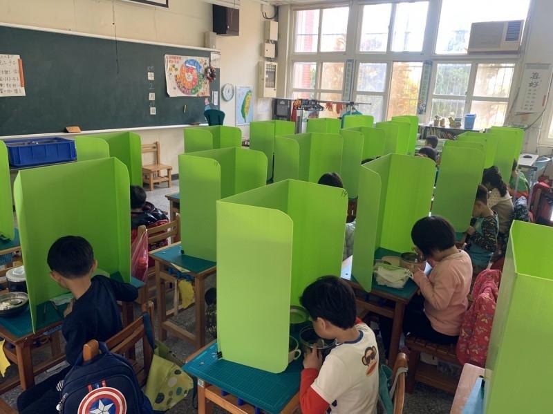 防疫減少飛沫出奇招!新竹市建功國小有一年級老師採用綠色的隔板來區隔學生。(記者洪美秀翻攝)