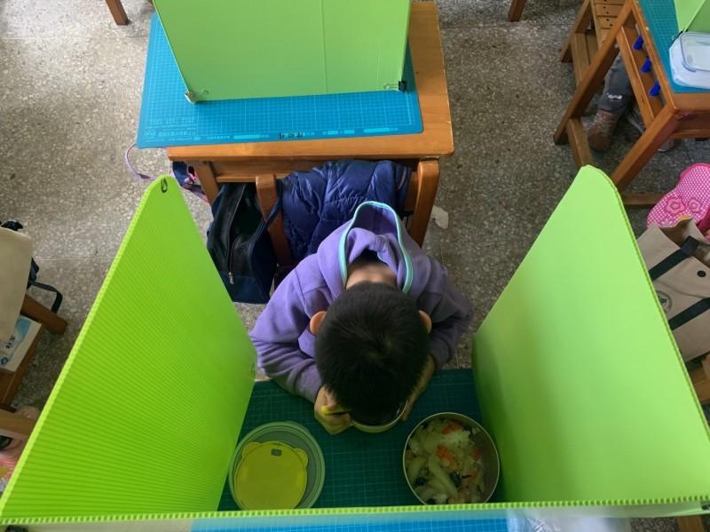 新竹市建功國小有一年級老師利用綠色的隔板來區隔學生,讓學生在用營養午餐時減少飛沫噴濺。(記者洪美秀翻攝)